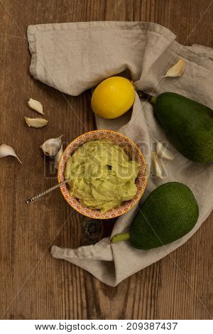 Upper view shot of an avocado sauce in a small bowl with entic pattern  and one lemon, two avocados and a few pieces of garlic placed over wooden rustic background