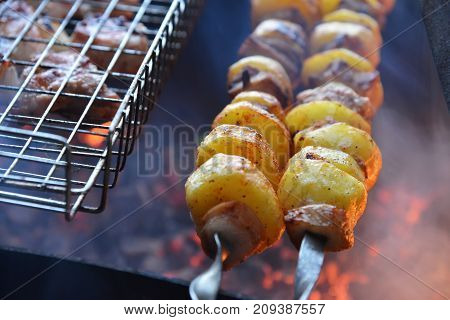 Grilled potato on the skewers with lard pieces on fire.