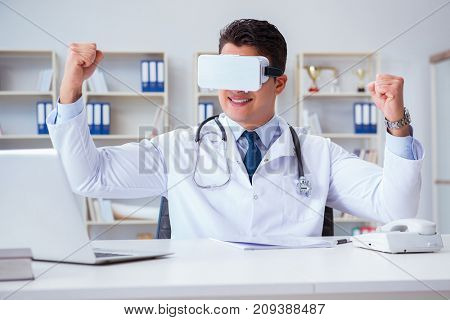 Young doctor with vr virtual reality headset working in the offi