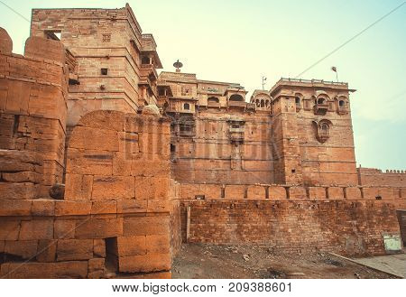 Birds over tall towers of historical Jaisalmer fort with monumental stone walls over the old city, India.