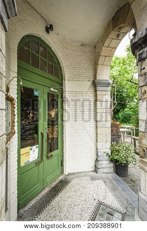 GHENT BELGIUM - JUNE 22 2016: A restaurant entrance with a big green door and an open space with tables and trees. Ghent Belgium.