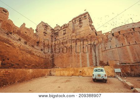JAISALMER, INDIA - Feb 1, 2016: Old white car parking past the historical Jaisalmer fort with stone towers in Thar desert on February 1, 2016. Jaisalmer has a population of about 78000.