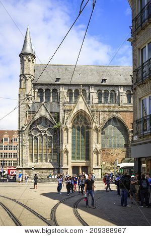 GHENT BELGIUM - JUNE 22 2016: Vertical picture of the side of Saint Nicholas' Church with tram rails and tourists in a sunny day with clouds. Ghent Belgium.