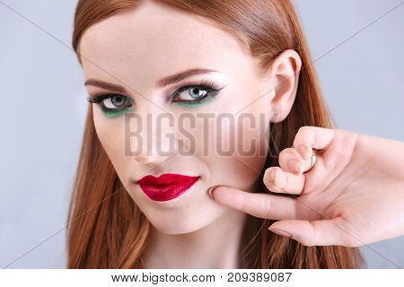 Beautiful redhead woman with bright green makeup on light background