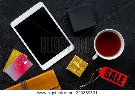 online payment for christmas present with credit card and tablet on dark black table background top view mockup
