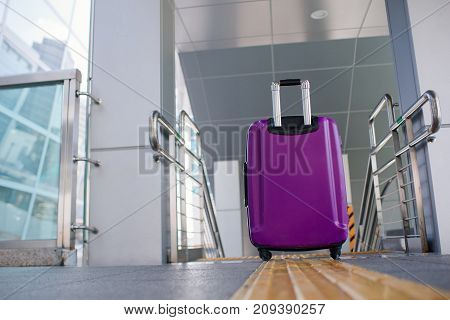 Suitcase on wheels  standing on the floor in modern airport terminal.
