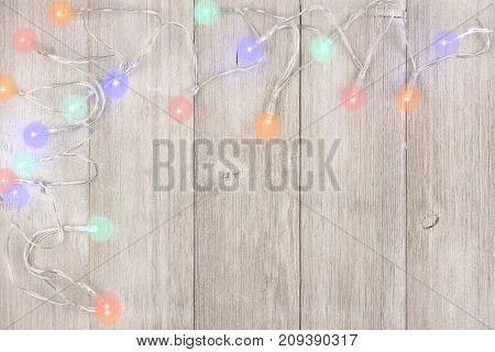 Twinkling Christmas Lights Corner Border, Above View On A Light Gray Wood Background
