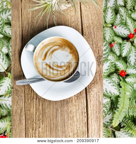 Cup of hot coffee on wooden table top view looking and green leaf with flower background