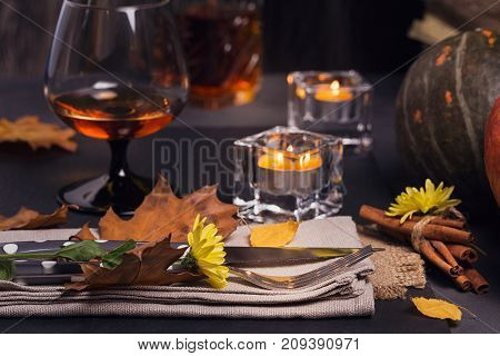 Table setting with autumn decoration for Thanksgiving. Dry leaves with cutlery and glass. Thanksgiving autumn background