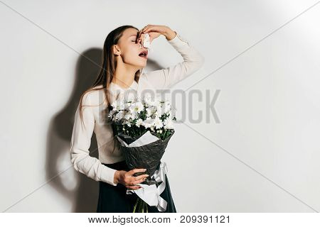 the girl holds a bouquet of flowers in her hands and sneezes because she is allergic