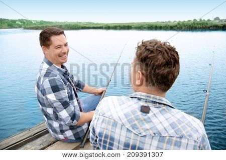 Two men fishing from pier on river