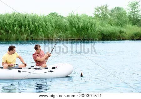 Two men fishing from inflatable boat on river