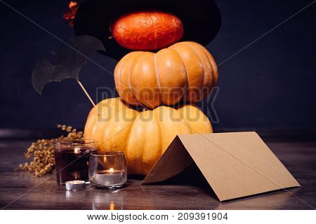 house decoration for Halloween, 3 pumpkins stand on top of each other, witch hat, burning candles, autumn leaves