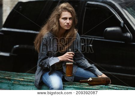 Woman sitting with bottle of alcohol near car