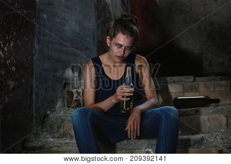 Woman sitting with bottle of alcohol in abandoned building