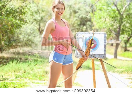 Young woman practicing archery outdoors