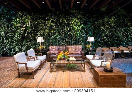 SAO PAULO BRAZIL - OCTOBER 07 2017: Wide angle picture of indoor room with nice furniture and wall with plants for a wedding party in the city of Sao Paulo Brazil.