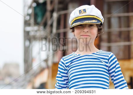 Portrait of a boy in a striped long sleeve T-Shirt (Telnyashka) and captain's cap.