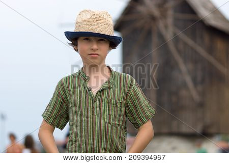 Portrait of a beautiful boy in a short shirt and hat on a blurred background of a wooden windmill.