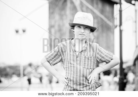 Portrait of a beautiful boy in a short shirt and hat on a blurred background. Black and white.