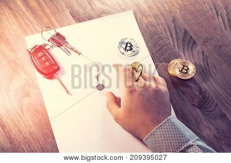 A Man Holds A Bitcoin Coin In His Hand Like A Chip From A Casino, Close To The Car Keys And From The