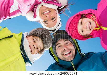 Smiling family with heads in a circle looking at camera in winter holiday. Portrait of happy young family with two children embracing outdoor. Group of happy skiers standing and looking at camera.