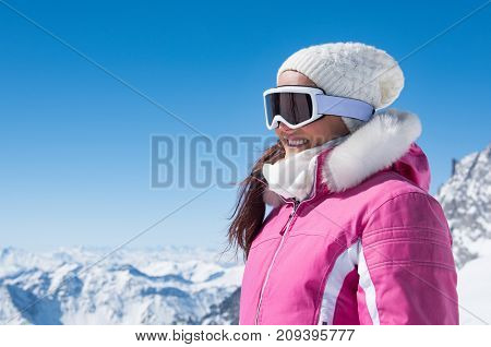 Young woman wearing ski glasses outdoor in winter. Smiling girl face wearing ski goggles with copy space. Beautiful woman looking away in snowy winter landscape.