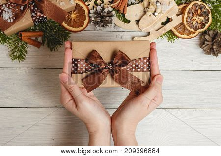 Top view Happy new year festival or Birthday and Merry Christmas day background concept. Hands holding the little present. Object on the modern light rustic wood at home office desk