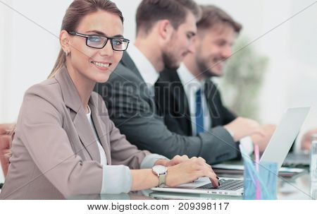 Portrait of happy business woman with  colleagues interacting on