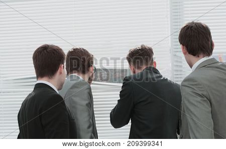 business team pushing the blinds and looking out the office wind
