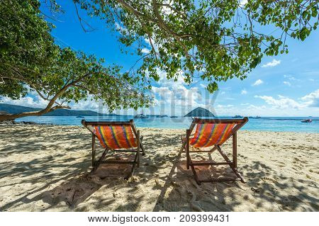 Sunbeds On A Paradise Island Under A Tree, Sunny Day By The Sea Shore Of A Resort
