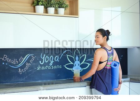 Portrait of smiling woman holding in her hand a yoga mat while standing at studio. Yoga. Woman. Wellness