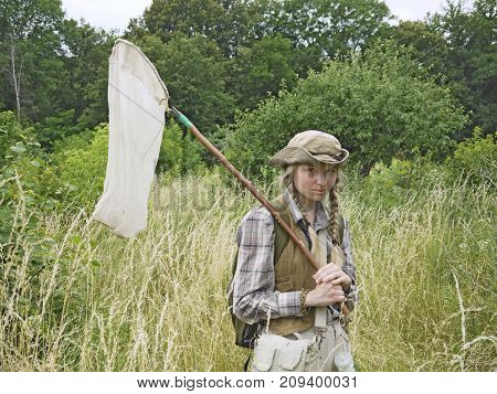 A girl entomologist in a field near a forest. A young woman is dressed in country style, has two plaits, wears a hat and holds an insect net. A student summer field period in the university.