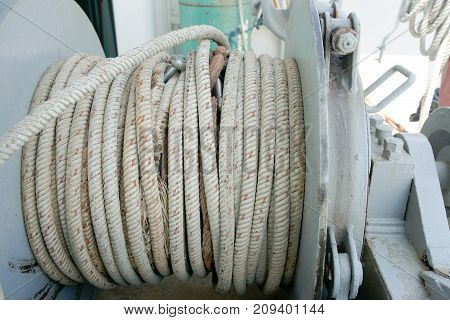 Anchor rope from a anchor winch on deck. The anchor is still inside the ship. Typical maritime background.