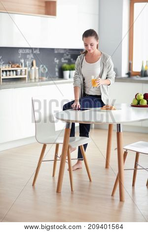 Young woman with orange juice and tablet in kitchen.