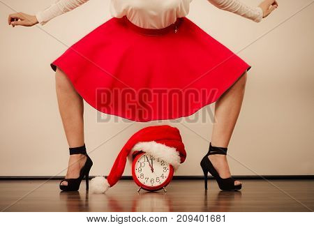 Closeup of woman in high heels and alarm clock with santa claus hat. Christmas time season concept.