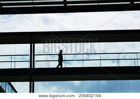 Silhouette view of a businessman in a modern office building interior with panoramic windows.