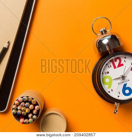 Collage with round clock pencil and notebook on orange background time concept.