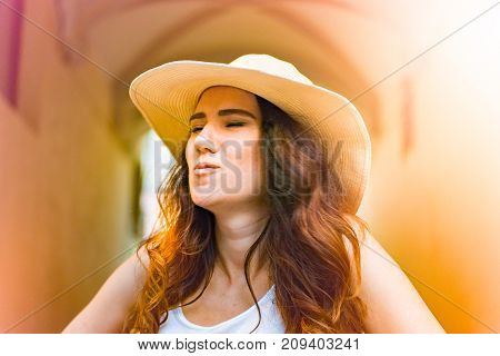 Girl with hat on summer day in the street, in architectural setting in a european city