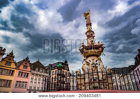 View of Hauptmarkt square in Trier, with historic fountain dating from 1595. Colorful facades in the central square Hauptmarkt with the monuments Petrusbrunnen and Market Cross
