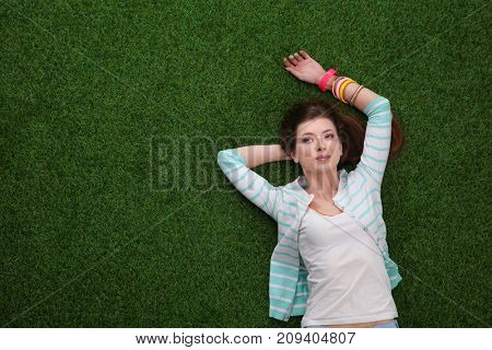 Beautiful redhead women lying down on green grass in summer time in the park