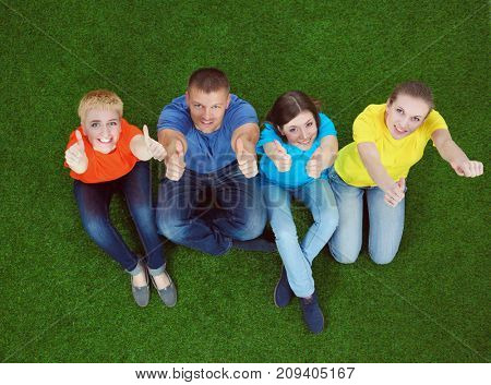 Group of young people sitting on green grass