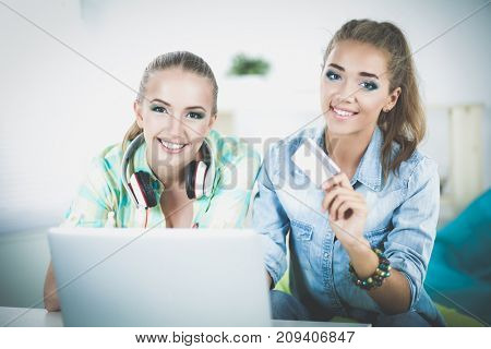 Two Woman shopping online with tablet and credit card