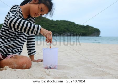 Cigarette and tobacco ashtray on the beach. Volunteer girl collecting butts and garbage on the sand. Marine pollution destructive nature environment.