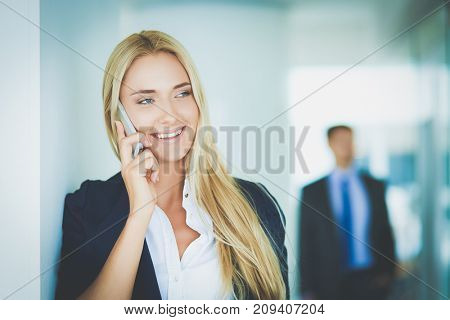 Businesswoman standing against office window talking on mobile phone