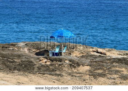 on the beach there is a blue umbrella