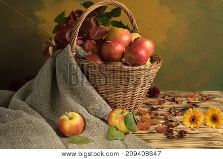 apples in a basket with autumn leaves and burlap