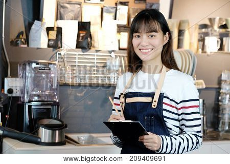 Young asian barista taking note order at coffee cafe counter with smiling face food and drink business concept