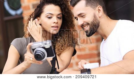 Portrait of a couple sitting down at a cafe and looking  photos