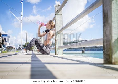 outdoor portrait of young attractive healthy girl doing sport exercise on urban background, sport and healthy lifestyle in the city